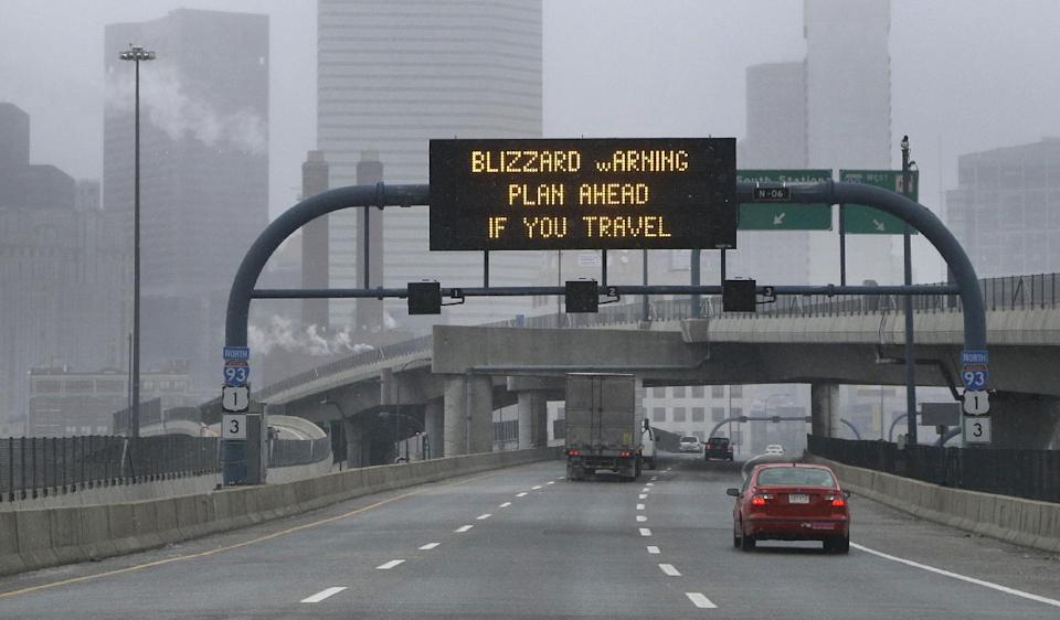 A warning sign flashes for motorists on the expressway into Boston as snow starts to fall on Friday, Feb. 8, 2013. A major winter storm is heading toward the U.S. Northeast with up to 2 feet of snow expected for a Boston-area region that has seen mostly bare ground this winter. (AP Photo/Elise Amendola)