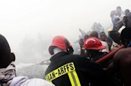 Firefighters work at the scene of the crash of a Dana Airline plane that plunged onto a plot containing a church, a two-storey residential building and a printing shop in Lagos. The plane carrying 153 people plunged into a residential area of Nigeria's largest city, with all those aboard presumed dead