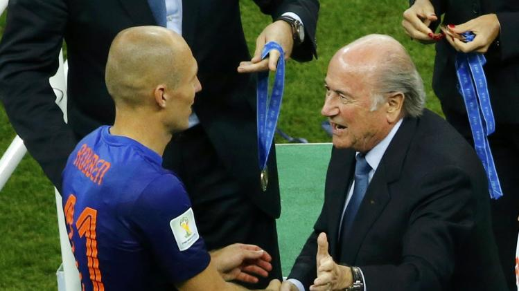 FIFA president Blatter congratulates Arjen Robben of the Netherlands after the 2014 World Cup third-place playoff against Brazil at the Brasilia national stadium in Brasilia