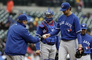 Toronto Blue Jays pitcher Josh Johnson, right, hands the ball to manager John Gibbons while being relieved in the second inning of a baseball game against the Detroit Tigers in Detroit, Thursday April 11, 2013. (AP Photo/Paul Sancya)