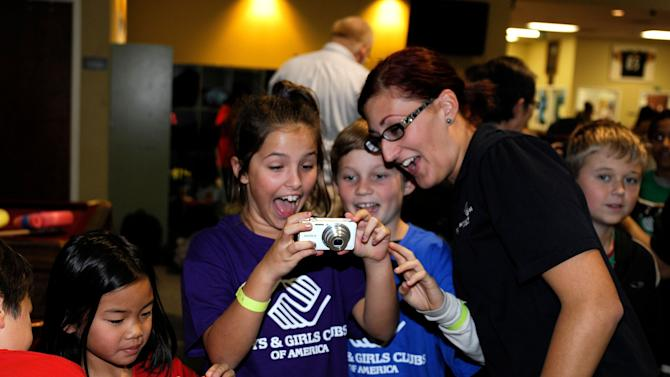 IMAGE DISTRIBUTED FOR BOYS & GIRLS CLUBS OF AMERICA - In this image released on Monday, Jan. 7, 2013, youth from Boys & Girls Clubs of San Dieguito gather around a camera during a photography event with Sony Electronics in San Diego. The event kicked off a national partnership between Boys & Girls Clubs of America and Sony, which seeks to engage Club youth nationwide to explore and build their skills in photography, digital arts and self-expression.  The San Diego Club event included photography workshops for youth using the latest Sony camera technology taught by Sony volunteers. It also featured a special visit by renowned photographer and Sony Artisan of Imagery, Matthew Jordan Smith, known for photographing top names in the entertainment industry. (Denis Poroy / AP Images for Boys & Girls Clubs of America)