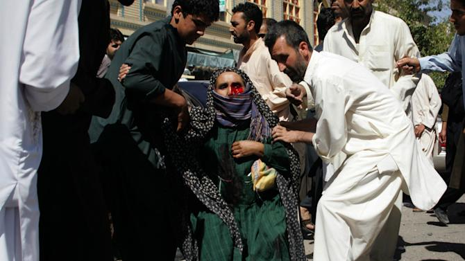 Afghans carry a wounded woman from the scene of an explosion in Herat, west of Kabul, Afghanistan, Wednesday, Aug. 15, 2012. Over a dozen people, including four women and a policeman, were injured when explosives set up on a bicycle exploded at a market in the city of Herat while people were shopping for an upcoming Muslim holiday, said Noor Khan Nekzad, a spokesman for the provincial police. (AP Photo/Hoshang Hashimi)