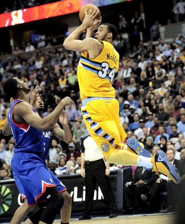 Denver Nuggets' McGee takes a shot over Philadelphia 76ers' Young and Moultrie during their NBA basketball game in Denver, Colorado