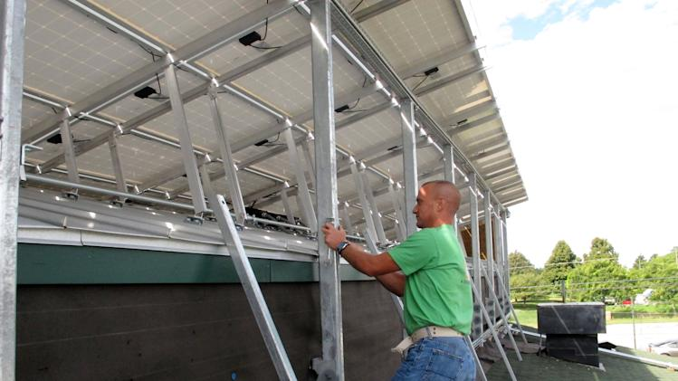 In this Sept. 6, 2011 photo, Tipping Point Renewable Energy employee Ben Noland works on a solar panel installation at Flannagan's bar in Dublin, Ohio. The solar power company is hiring military veterans like Noland for its crews at a time when unemployment among former service members is outpacing that of civilians. (AP Photo/Kantele Franko)
