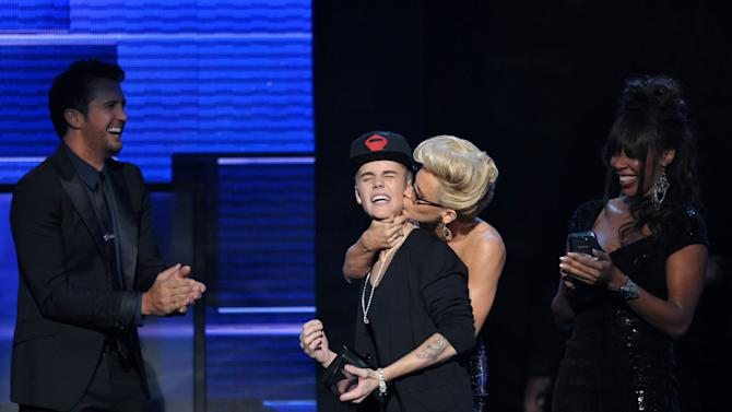 "Justin Bieber is smothered in kisses by presenter Jenny McCarthy as he accepts the award for favorite album - pop/rock for ""Believe"" at the 40th Anniversary American Music Awards on Sunday, Nov. 18, 2012, in Los Angeles. (Photo by John Shearer/Invision/AP)"