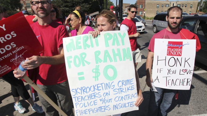 Chicago public school teachers walk a picket line outside Lane Tech High School on Tuesday, Sept. 11, 2012, on the second day of a strike in the nation's third-largest school district. Negotiations by the two sides failed to come to an agreement Monday in a bitter contract dispute over evaluations and job security. (AP Photo/Robert Ray)