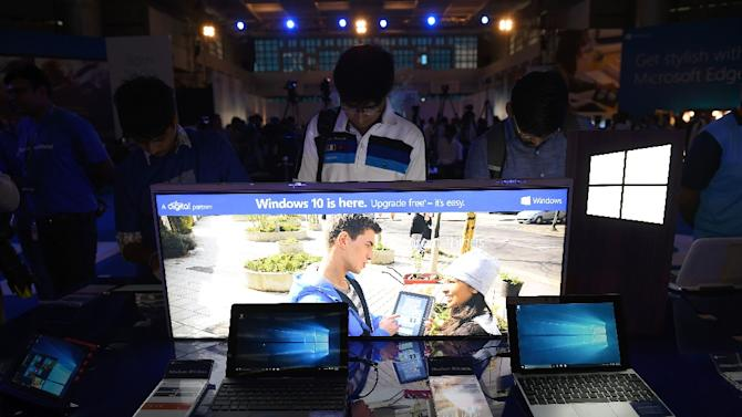 Indian visitors work on computers and tablets loaded with the newly launched Windows 10 at an event in New Delhi on July 29, 2015