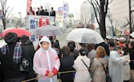 &lt;p&gt;People listen to an election campaign speech by Prime Minister Yoshihiko Noda (background C) of the ruling Democratic Party of Japan, a day before lower house election, in Tokyo, on December 15, 2012. Voters in Japan go to the polls on Sunday in an election likely to return long-ruling conservatives to power after three years in the wilderness.&lt;/p&gt;