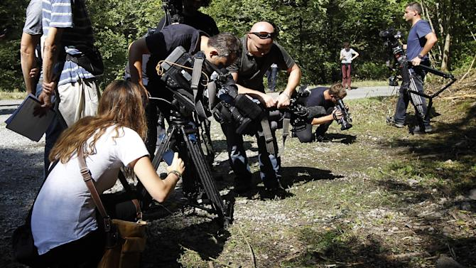 Journalists document the crime scene where four people were shot to death in a British-registered car, in a forest in the Alps, near Chevaline, France, Friday, Sept. 7, 2012. The case took on international ramifications, with links that tied the slain family to Britain, Iraq and Sweden. (AP Photo/Laurent Cipriani)