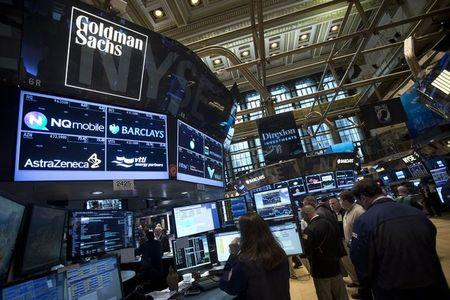 The Goldman Sachs logo is pictured on their post as traders work on the floor of the New York Stock Exchange in New York