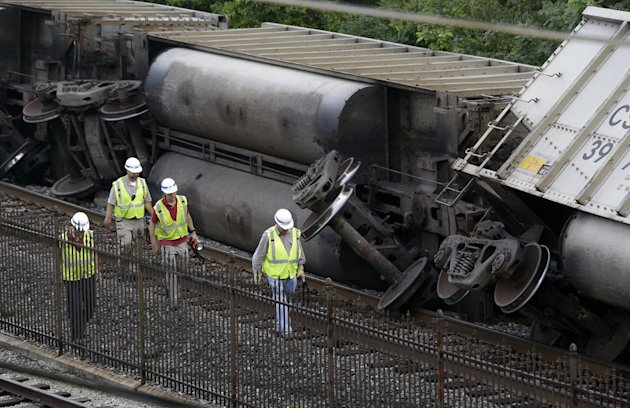 Officials walk past part of a CSX freight trail that derailed overnight in Ellicott City, Md., Tuesday, Aug. 21, 2012. Authorities said two people not employed by the railroad were killed in the incident. (AP Photo/Patrick Semansky)