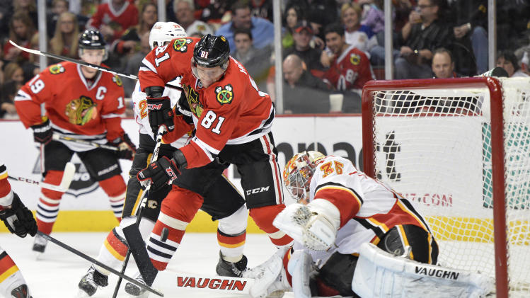 Chicago Blackhawks' Marian Hossa of Slovokia, left, tries to score on Calgary Flames goalie Joey MacDonald during the second period of an NHL hockey game, Friday, April 26, 2013 in Chicago.  (AP Photo/Brian Kersey)