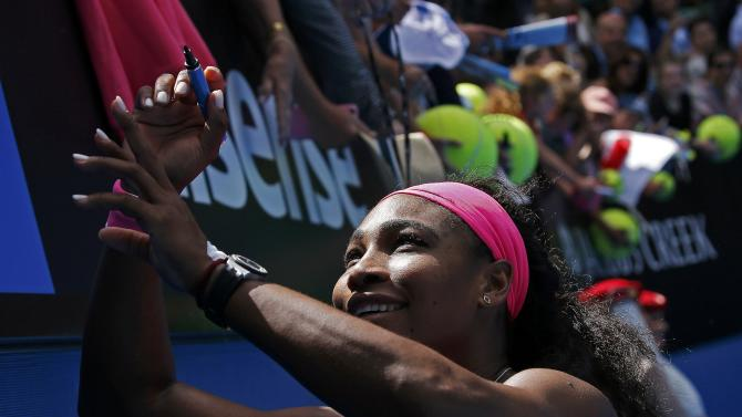 Serena of the U.S. signs autographs after defeating Cibulkova of Slovakia to win their women's singles quarter-final match at the Australian Open 2015 tennis tournament in Melbourne