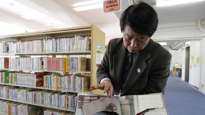 "A ripped copy of Anne Frank's ""Diary of a Young Girl"" picture book is shown by Shinjuku City Library Director Kotaro Fujimaki at the library in Tokyo Friday, Feb. 21, 2014. Tokyo Libraries said on Friday that hundreds of copies of Anne Frank's diary and related books have been found vandalised across the city's libraries in the last month, sparking fears of an anti-Semitic motive. A total of 265 books in 31 libraries had been found damaged after the first damaged book was found in January, prompting a wider search. (AP Photo/Koji Ueda)"