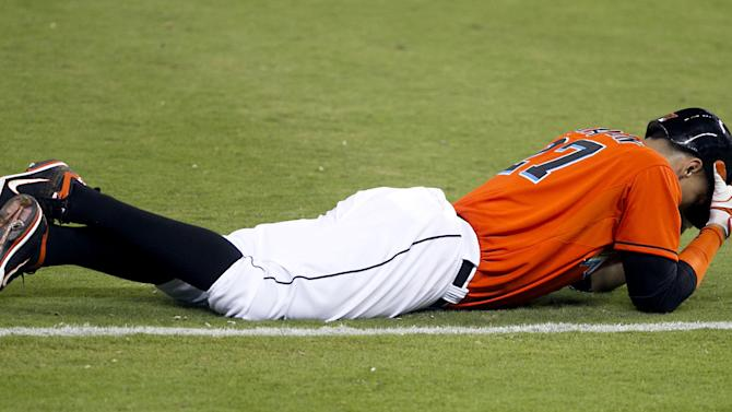 Miami Marlins' Giancarlo Stanton holds his head after being injured in the 10th inning of a baseball game against the New York Mets at Marlins Park in Miami on Monday, April 29, 2013. (AP Photo/The Miami Herald, Joe Rimkus Jr.)
