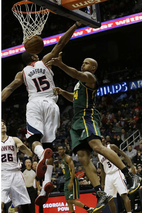 Utah Jazz small forward Richard Jefferson (24) passes around Atlanta Hawks center Al Horford (15) in the first half of an NBA basketball game on Friday, Dec. 20, 2013, in Atlanta