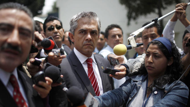 FILE - In this Aug. 20, 2010 file photo, Mexico City's Attorney General Miguel Angel Mancera, center, looks on during the presentation of a new elite police group in Mexico City. Mancera, who is running for mayor of Mexico City, holds an astonishing lead of about 50 points in polls going into the July 1 vote, which coincides with the 2012 presidential election. Mancera is campaigning on his reputation as the city's attorney general and a 12 percent drop in crime from 2010 to 2011.  (AP Photo/Alexandre Meneghini, File)