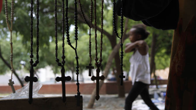 A young girl walks past rosaries hanging at a hawkers stall in Freedom Square, Soweto, South Africa, Monday, Dec 10, 2012. Various leaders and personalities have called for people to pray for former president Nelson Mandela as he underwent more unspecified medical tests in a military hospital in Pretoria as the public and journalists outside continued to ask the same, as of yet unanswered questions: What, if anything, is wrong with the 94-year-old anti-apartheid icon. (AP Photo/Denis Farrell)