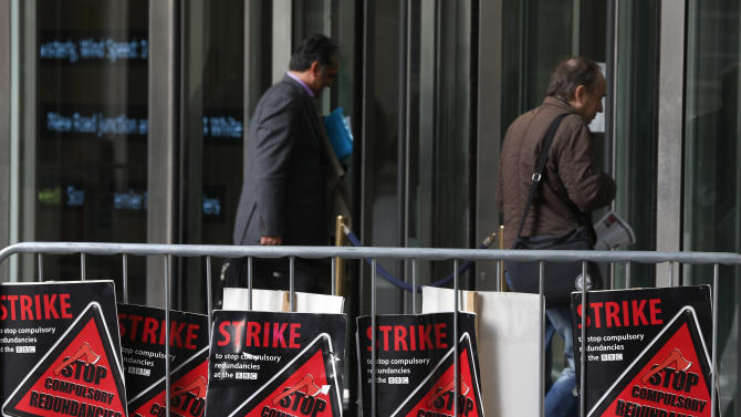 Placards are seen as BBC journalists mount picket lines after launching a 24-hour strike in a row over jobs, outside the BBC Broadcasting House, in central London, Monday, Feb. 18, 2013. (AP Photo/Lefteris Pitarakis)