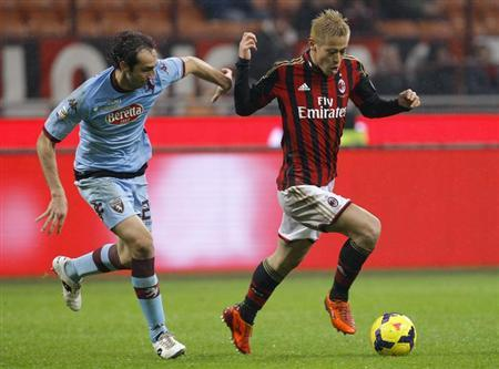 AC Milan's Keisuke Honda (R) fights for the ball with Torino's Emiliano Moretti during their Italian Serie A soccer match at the San Siro stadium in Milan February 1, 2014. REUTERS/Alessandro