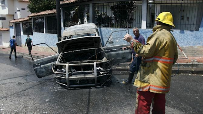 Firefighters hose down a National Guard patrol vehicle that was burned by anti-government protesters in San Cristobal