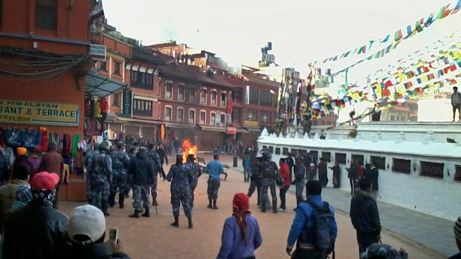 Nepalese policemen rush towards an exiled Tibetan Buddhist monk, center, who self immolated at Boudhanath Stupa in Katmandu, Nepal, Wednesday, Feb. 13, 2013. A police official says the Tibetan man has set himself on fire in Nepal's capital in what is believed to be the latest self-immolation to protest Chinese rule in Tibet. (AP Photo)