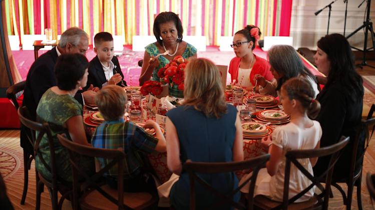 "FILE - In this Aug. 20, 2012 file photo, First lady Michelle Obama sits with Michael Prados, left, from Louisiana, and Ilianna Gonzales-Evans, right, from Washington, and others, during the first Kids' ""State Dinner,"" in the East Room of the White House in Washington. Children from across the nation will rub elbows with Michelle Obama and dine off fine china in the East Room of the White House this summer as part of a contest to promote healthy eating. The first lady is asking children ages 8 to 12 and their parents to create nutritious lunch recipes that represent each of the food groups for ""The Healthy Lunchtime Challenge."" (AP Photo/Pablo Martinez Monsivais, File)"