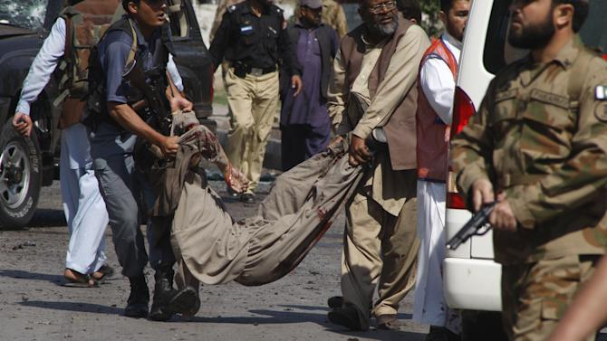 A Pakistani police officer and a rescue worker remove a dead body from the site of suicide bombing in Peshawar, Pakistan on Friday, March 29, 2013. A suicide bomber struck a security convoy carrying a paramilitary police commander in northwestern Pakistan, killing several people — including two women, but the commander escaped unhurt in the blast in Peshawar. Concerns are rising that the militants could step up the pace of attacks ahead of May parliamentary elections. (AP Photo/Mohammad Sajjad)