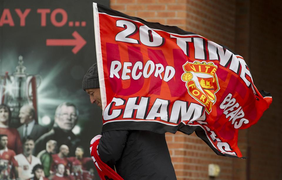 A merchandise seller walks in front of a poster at Manchester United's Old Trafford Stadium, Manchester, England, Thursday May 9, 2013.  It was announced on May 8 that long serving manager Alex Ferguson would soon be retiring after 26 years in charge at the club. (AP Photo/Jon Super)