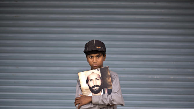 Ali Haider, 10, poses for a portrait holding a photograph of his father, who went missing on July 14, 2010, while he and other relatives take a break from a long march protest, in Rawalpindi, Pakistan, Friday, Feb. 28, 2014. Ten-year-old Ali Haider has spent the last four months of his life walking across the breadth of Pakistan in an effort to find out what has happened to his father who has been missing since 2010. Haider is the youngest of two dozen activists from the impoverished southwestern province of Baluchistan who walked roughly 3,000 kilometers (1,860 miles) to the capital of Islamabad to draw attention to alleged abductions of their loved ones by the Pakistani government. (AP Photo/Muhammed Muheisen)