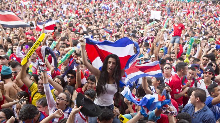 Costa Rica soccer fans celebrate a goal against Greece as they watch the World Cup round of 16 match on TV set up in a public square in San Jose, Costa Rica, Sunday, June 29, 2014. (AP Photo/Esteban Felix)