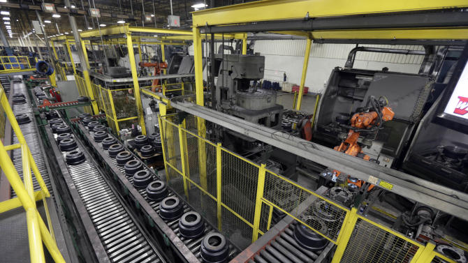In this Friday, Jan. 11, 2013, photo, brake drums roll down a conveyor belt to a station which robotically balances the drum at Webb Wheel Products in Cullman, Ala. Webb Wheel hasn't added a factory worker in three years, though it's making 300,000 more drums annually, a 25 percent increase, because of robots. (AP Photo/Dave Martin)
