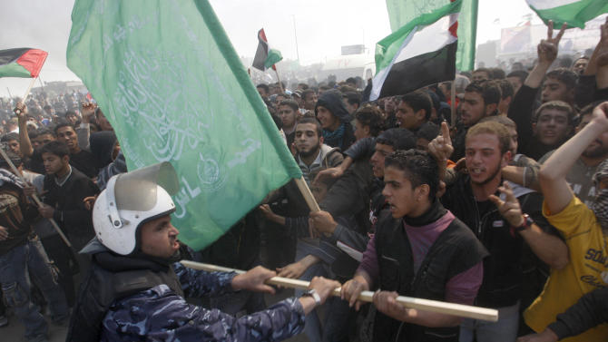 """A Hamas security officer tries to prevent protesters from reaching Erez crossing during a march heading towards the border with Israel in the northern Gaza Strip, Friday, March 30, 2012. Israeli security forces in riot gear Friday confronted Palestinian demonstrators on """"Land Day"""". The """"Land Day"""" rallies are an annual event marked by Israeli Arabs and Palestinians in the West Bank and Gaza who protest what they say are discriminatory Israeli land policies.(AP Photo/Hatem Moussa)"""