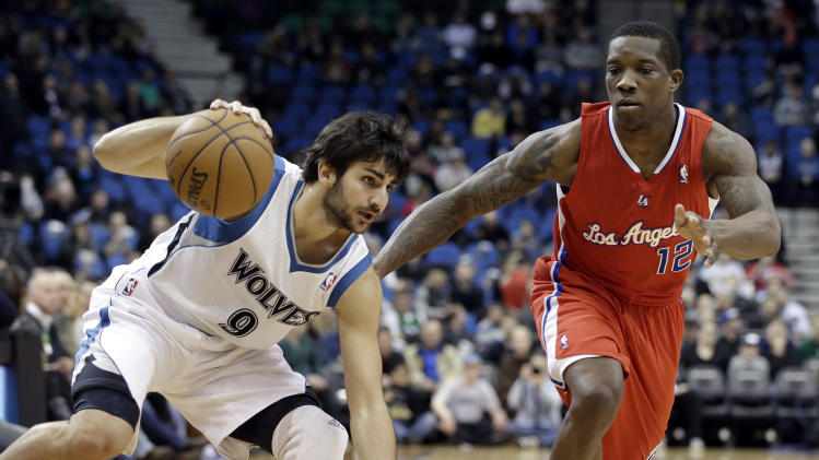 Minnesota Timberwolves' Ricky Rubio of Spain, left, maintains his balance as he drives past Los Angeles Clippers' Eric Bledsoe in the first half of an NBA basketball game Wednesday, Jan. 30, 2013 in Minneapolis. (AP Photo/Jim Mone)