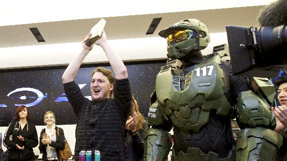 Peter Gagnon celebrates purchasing the first copy of Halo 4 during the game's launch, on Monday, Nov. 5, 2012 in Seattle. At right, Halo character Master Chief. (Photo by Stephen Brasher/Invision for Xbox/AP Images)