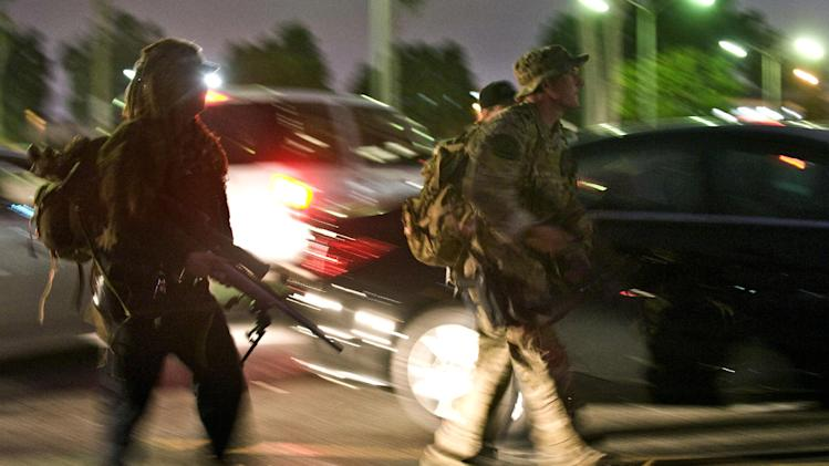 SWAT team members cross the parking lot of the Cal State Fullerton Communications Building toward positions near the Mihaylo College of Business and Economics, Wednesday, Dec. 12, 2012, in Fullerton, Calif. Students were placed on lock down as police searched for two suspects in a jewelry store robbery, who were considered armed and dangerous. (AP Photo/The Orange County Register, Bruce Chambers)