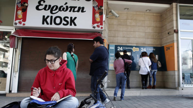 A kiosk with the name Europe written in Greek, is closed as people use the ATMs outside a closed branch of the Bank of Cyprus in capital Nicosia, Cyprus, Wednesday, March 27, 2013. Cypriot authorities are preparing limits on how much money depositors can take out of their accounts a day before banks are set to reopen. (AP Photo/Petros Giannakouris)