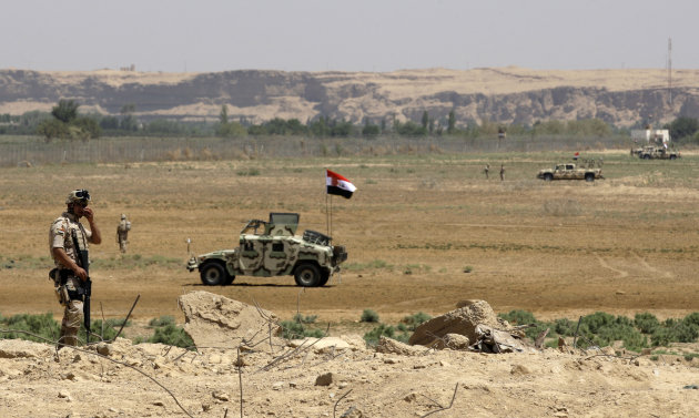 Iraqi soldiers patrol along the border between Syria and Iraq in Qaim, located in the Euphrates river valley 200 miles (320 kilometers) west of Baghdad, Iraq, Friday, July 20, 2012. Syrian rebels maintained control for a second day of the crossing at the Iraqi border town of Qaim on Friday, Iraqi government spokesman Ali al-Dabbagh said. (AP Photo/Khalid Mohammed)