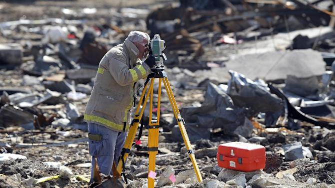 A forensic mapper works measuring the crater at the site of the fire and explosion in West, Texas on Wednesday, April 24, 2013. The explosion at West Fertilizer which killed 14 people left a crater more than 90 feet (27 meters) wide and blasted the walls and windows off dozens of buildings in the town of 2,700. (AP Photo/The San Antonio Express-News, Tom Reel, Pool)