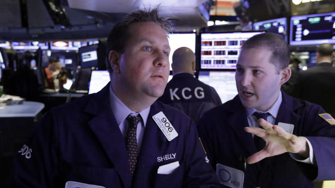 Specialists Jeffrey Sheldon, left, and David Vail confer at a post on the floor of the New York Stock Exchange Monday, Dec. 9, 2013. The stock market is opening little changed following last week's strong U.S. jobs report. (AP Photo/Richard Drew)