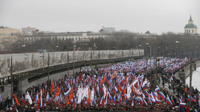 People march behind a large banner to commemorate Kremlin critic Boris Nemtsov, who was shot dead on Friday night, in central Moscow