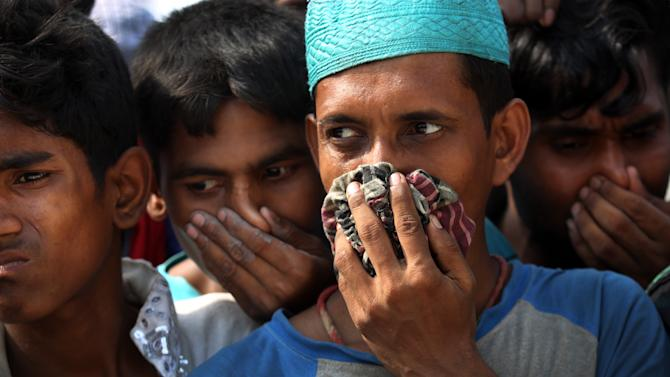 People cover their noses to block out the smell of decomposing bodies as a truck transporting unclaimed bodies from the garment factory building that collapsed last week arrives for a mass burial, Wednesday, May 1, 2013, in Dhaka, Bangladesh. Several hundred people attended a mass funeral in a Dhaka suburb for 18 unidentified workers who died in the building collapse last week in the country's worst industrial disaster, killing at least 402 people and injuring 2,500.   (AP Photo/Wong Maye-E)