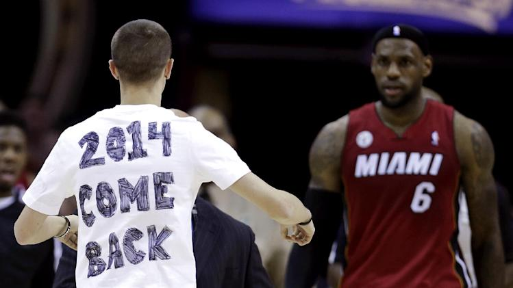 A fan runs out on the court towards Miami Heat's LeBron James during the fourth quarter of an NBA basketball game against the Cleveland Cavaliers on Wednesday, March 20, 2013, in Cleveland. Miami won 98-95. (AP Photo/Tony Dejak)