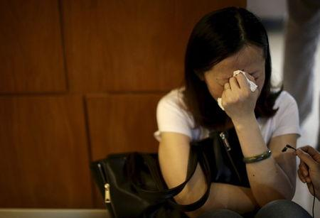 A family member of passengers on the ship which sank at the Jianli section of Yangtze River cries in Shanghai
