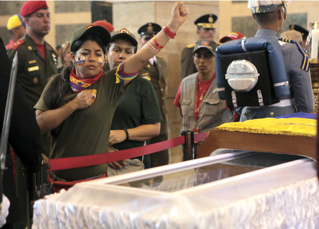 In this photo released by Miraflores Press Office, a woman pays her respects, placing a hand on her heart and saluting,  before she files past the glass-topped casket containing the remains of Venezue