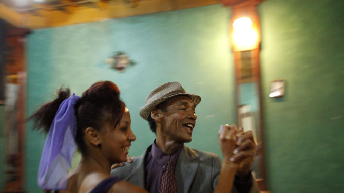 """This April 26, 2012 photo shows performers dancing to live music at Casa de la Trova, house of troubadors, in Santiago de Cuba, Cuba.  Music is an integral part of Cuban culture, particularly in Santiago de Cuba, birthplace of composer Compay de Segundo, who was well known before, but became an international celebrity when the Ry Cooder film, """"The Buena Vista Social Club"""" was released. (AP Photo/Kathy Willens)"""