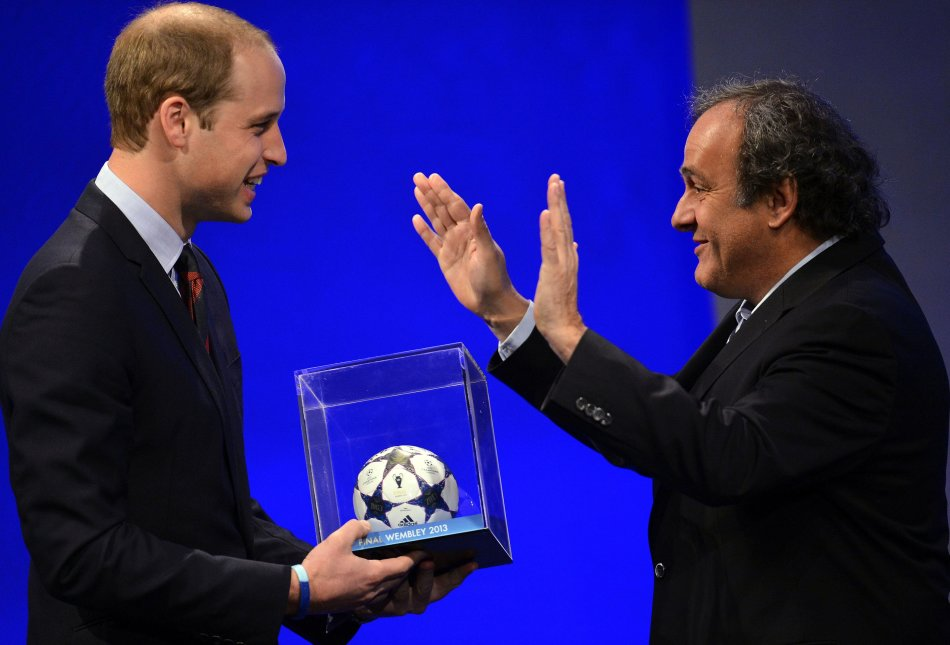Britain's Prince William, the Duke of Cambridge, reacts as he is presented with a mini-football by UEFA President Michel Platini in central London