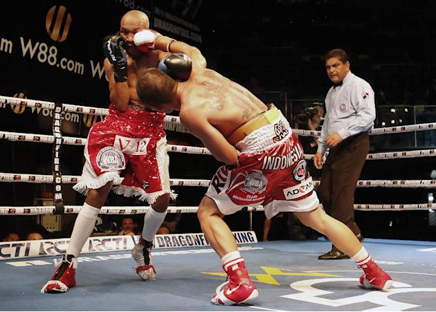 Indonesia's WBO Super featherweight champion Chris Johns , right,  connects with a right hook against IBO champion South African's Simpiwe Vetyeka during their Super Featherweight title fight