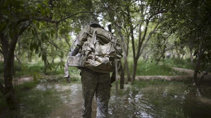 FILE - A U.S. Army soldier crosses an irrigated field during a patrol by the 1-320th Alpha Battery, 2nd Brigade of the 101st Airborne Division near COP Nolen, in the Arghandab Valley, Kandahar, Afghanistan, Friday, July 23, 2010. (AP Photo/Rodrigo Abd, File)