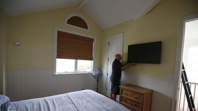 Vybourg looks at a audio visual equipment he installed in a home in Manhattan Beach